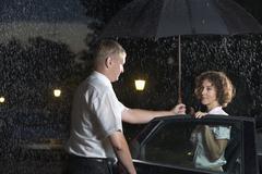 A man opening a car door and holding an umbrella over a woman Stock Photos