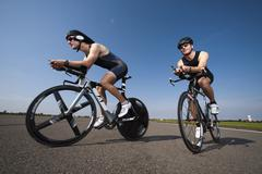 Two cyclists on racing bicycles, side view, low angle view - stock photo