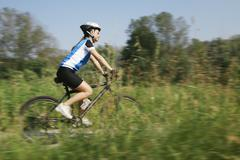 young woman training on mountain bike and cycling in park - stock photo
