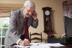 A businessman on a cell phone and doing paperwork at home Stock Photos