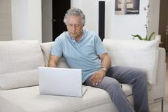 A senior man sitting on a couch using a laptop Stock Photos
