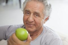 A senior man preparing to eat a green apple Stock Photos