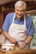 A senior man preparing food at home Stock Photos