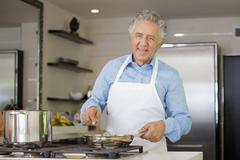 A cheerful man cooking in a domestic kitchen - stock photo
