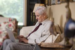 A businessman using a laptop at home Stock Photos