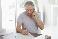 A senior man using the phone and writing on a document Stock Photos