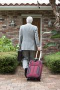 Stock Photo of A businessman arriving home from a trip