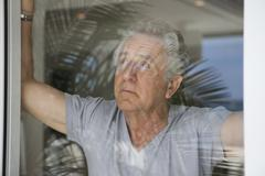 A senior man looking out a window Stock Photos