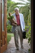 Stock Photo of A senior man arriving home with a bag of groceries and a briefcase