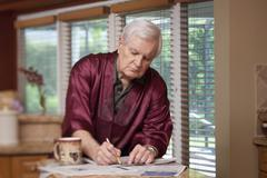 A senior man in a silk robe writing on a newspaper - stock photo