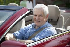 A cheerful senior man driving a convertible sports car - stock photo