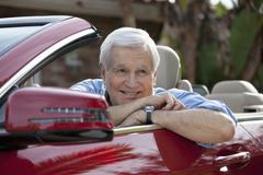 A senior man leaning on the door of his convertible sports car - stock photo