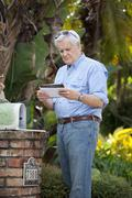A senior man standing by his mailbox, looking at mail - stock photo
