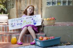 Girl selling apples on the front porch - stock photo
