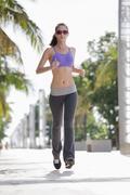 Girl jogging on pavement Stock Photos