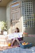 Girl selling apples on front porch and holding sign - stock photo