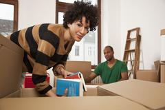A couple packing moving boxes - stock photo