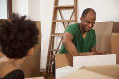 A couple packing moving boxes, focus on man - stock photo