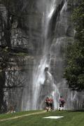 Hikers walking towards a waterfall, Chiavenna, Lombardy, Italy Stock Photos