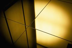 Close-up spot lit reflection in yellow toned mirrors Stock Photos