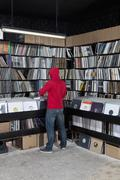 A young man looking through records at a record store, rear view - stock photo