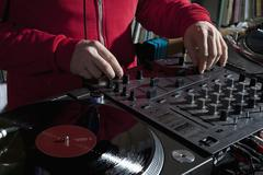 A DJ adjusting knobs on a sounder mixer, detail of hands Stock Photos