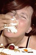 Woman eating cake with hand Stock Photos