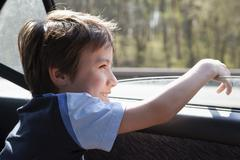 A child looking out a car window Stock Photos