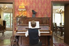 A boy practicing on an old-fashioned upright piano - stock photo