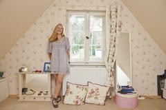A teengirl standing in her bedroom smiling - stock photo