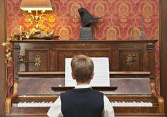 A boy practicing on an upright piano Stock Photos