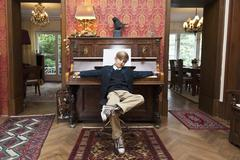 A boy with a cool attitude posing at an old-fashioned upright piano - stock photo
