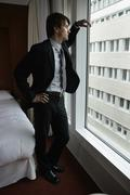 Man in suit standing at window Stock Photos