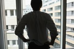 Businessman standing at window Stock Photos