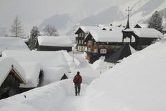 Man strolling through snow covered village Stock Photos