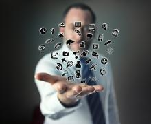Hand with cloud of application icons flying around Stock Photos