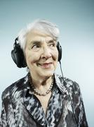 A senior woman wearing headphones Stock Photos