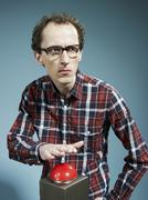 A nerdy guy with his hand poised above a red game show buzzer Stock Photos