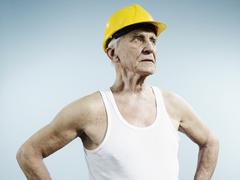 A senior man wearing a hardhat and tank top - stock photo