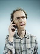 A man using a mobile phone with a confused look on his face - stock photo