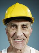 Headshot of a senior man wearing a yellow hardhat - stock photo