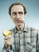 A man with a cheek bulging with a bite of apple, looking to the side - stock photo