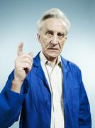 A senior man wearing coveralls and pointing while talking - stock photo