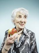 A senior woman holding an apple with a bite out of it - stock photo