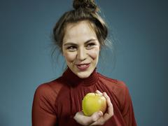 Stock Photo of A hip young woman holding an apple and smiling
