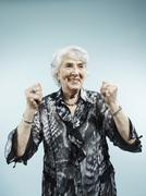 A senior woman with her arms raised in celebration Stock Photos