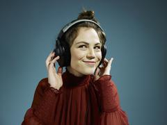 A young hip woman wearing headphones and smiling Stock Photos