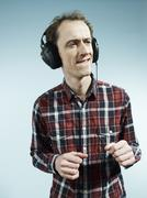 A nerdy guy biting his lip and dancing while listening to headphones - stock photo
