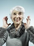 A senior woman with her arms raised in surprise - stock photo
