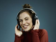 A young hip woman wearing headphones and smiling - stock photo